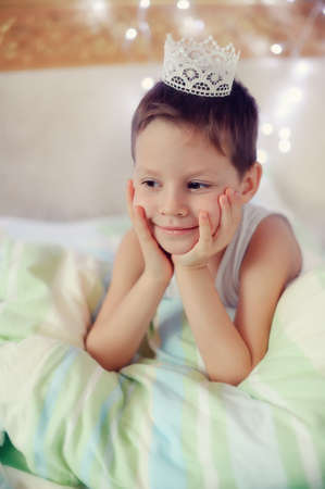 the boy woke up and is sitting in bed with a crown on his head photo