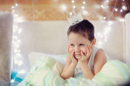 the boy woke up and is sitting in bed with a crown on his head Stock Photo - 16898768