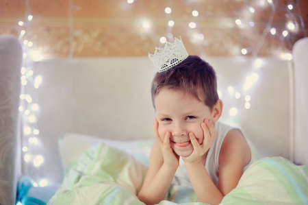 the boy woke up and is sitting in bed with a crown on his head