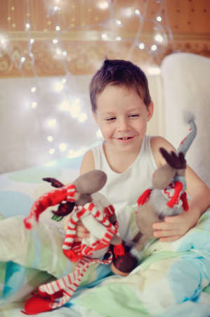 the boy woke up and sat on the bed with toy reindeer photo