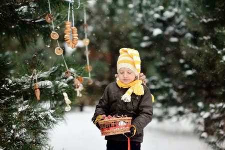 snowy winter outdoors boy dresses up Christmas tree bagels and toys Stock Photo - 16972272