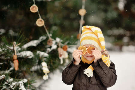 snowy winter outdoors boy plays with dried orange Stock Photo - 16972268