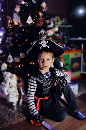 The boy in clothes of the pirate against a New Year tree poses Stock Photo - 17077045