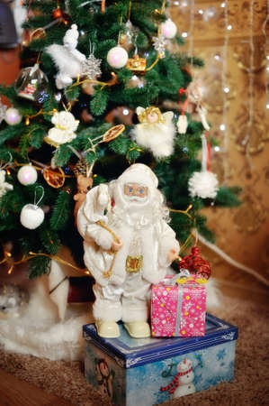Under a beautiful New Year tree there is Santa Claus with gifts Stock Photo - 17104846