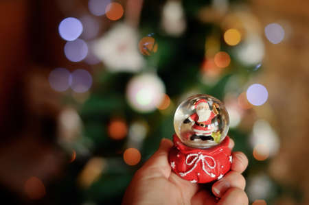 Against a New Year tree in a hand a sphere with Santa Claus Stock Photo - 17104284