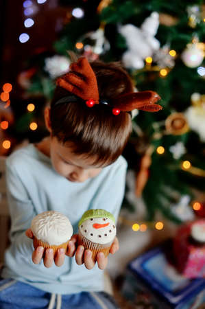 The boy with small horns of a deer under a New Year tree with beautiful fruitcakes in hand photo