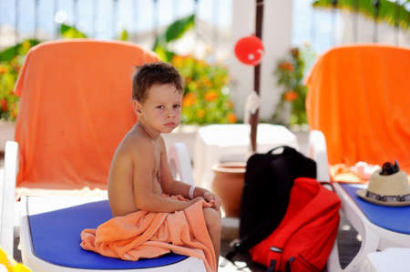 suppressed: The upset boy sits on a chaise lounge under a canopy covered by a towel