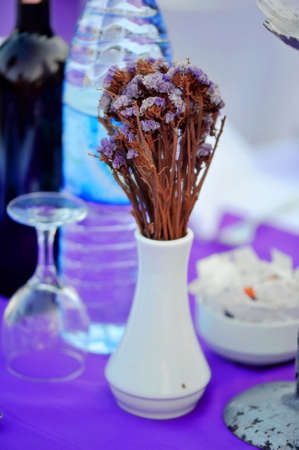 On a violet table there is a white base with dry wild flowers Stock Photo - 17400072
