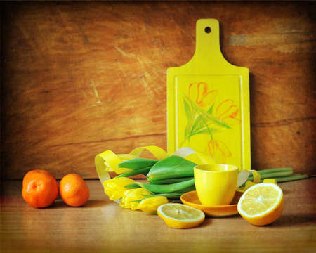On a brown background a yellow board with tulips and segments of a lemon of a tangerine photo