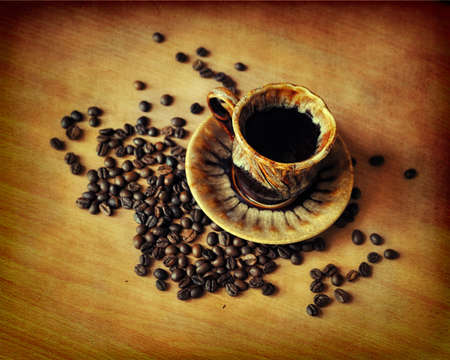 On a brown background a cup with hot fragrant coffee and grains photo
