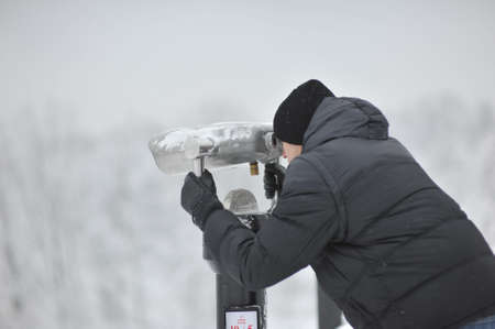 winter man in a black jacket and hat looking through binoculars photo