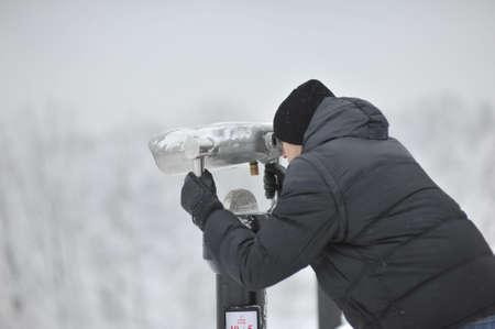 birdwatcher: winter man in a black jacket and hat looking through binoculars Stock Photo