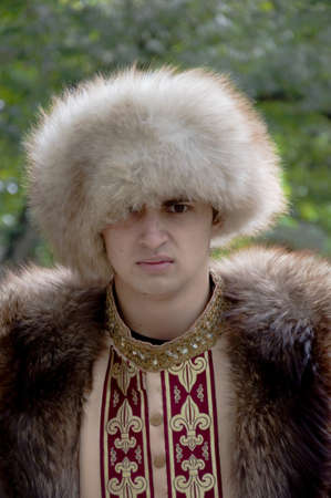 nobleman: The young man in a theatrical suit of a nobleman and in a fur cap poses on the nature