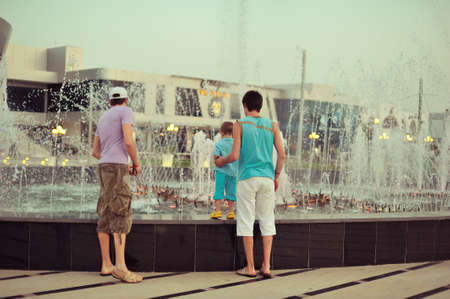 near the beautiful fountain walking people in a spray of water Stock Photo - 17508916