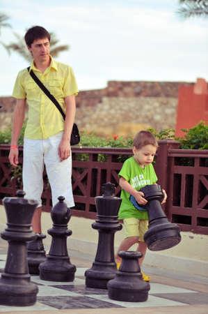 draußen im Park Vater und Sohn spielen mit den Big Playern im Schach