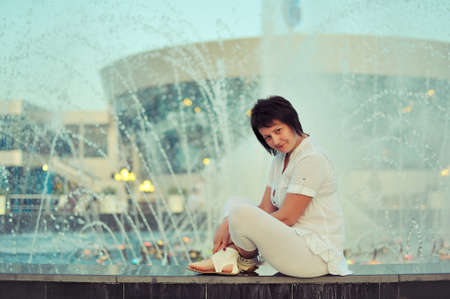 against splashing fountain sits a woman in a white suit photo