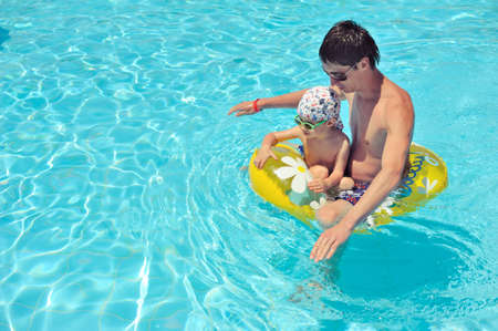 son with his father on a yellow circle swimming in a pool with clear water photo