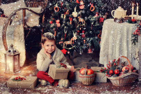 A handsome boy sitting on the floor with gifts and baskets at the Christmas tree photo