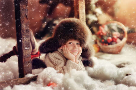 creative photo card is a smiling boy in a fur hat Standard-Bild