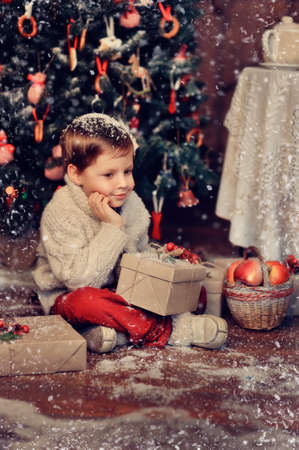 boy  with a basket of toys in the background of a beautiful Christmas tree photo