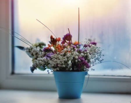 against the window of the small bouquet of colorful flowers in a blue Stock Photo - 17780253