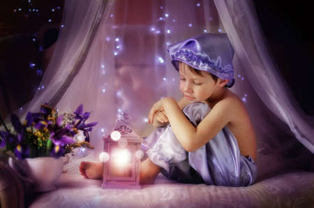 boy in pajamas and a purple hat sitting in the shed with a flashlight photo