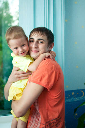 kindly: gently and kindly young man hugging his little nephew
