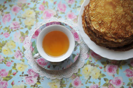Color porcelain cup with tea and a saucer with pancakes photo