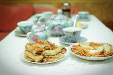 white table with china sets and big meals with delicious pancakes photo