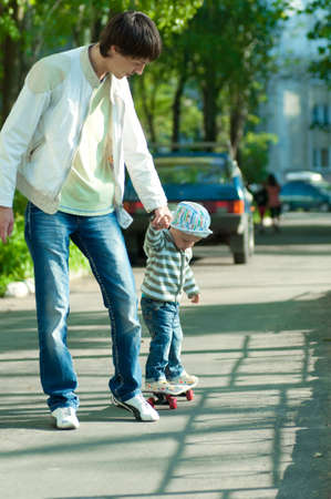 Father and son riding in the street on a skateboard photo