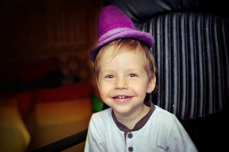 little boy in a purple hat and a white jacket fun grimacing Stock Photo