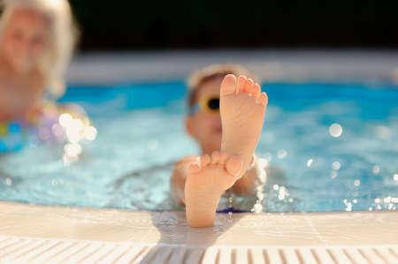 piedi nudi ragazzo: giornata di sole caldo, il ragazzo con occhiali da sole galleggiante in piscina vistaviv piedi nudi