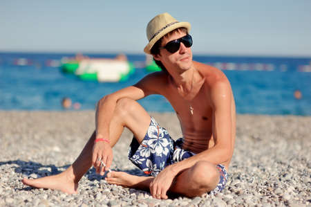 young man in sunglasses and a straw hat sitting on the beach photo
