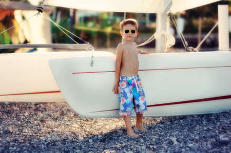 boy on the beach in shorts and sunglasses standing by the boat