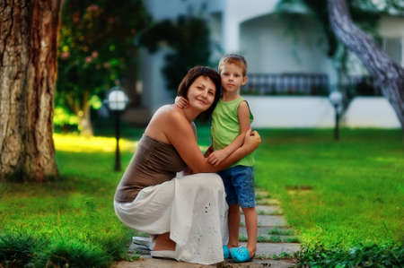 single parent: outdoors in the park mother and son on a walk hug Stock Photo