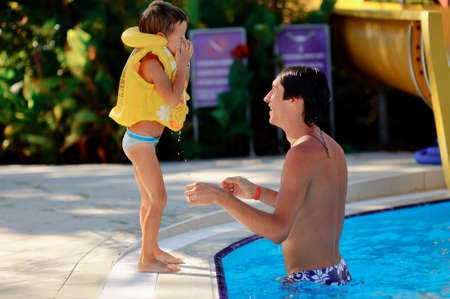 hot sunny day, the father and son playing in the blue water of the pool photo