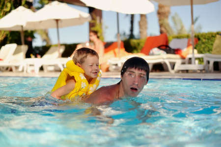 hot day a little boy in a yellow life jacket and dad swimming in the pool photo