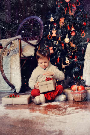 boy  with a basket of toys in the background of a beautiful Christmas tree Stock Photo - 18035729