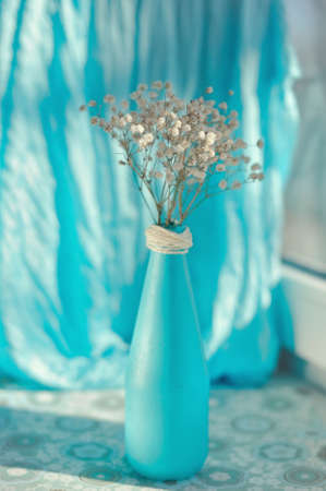 on a blue background and a blue vase delicate white flowers Stock Photo