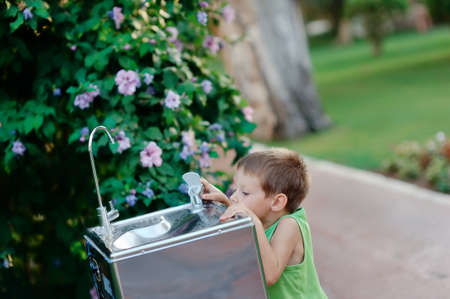 little boy reaching for the tap water in the street to get a drink of water photo