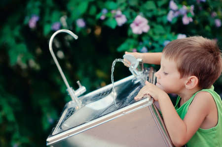 slurp: little boy reaching for the tap water in the street to get a drink of water