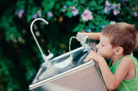 sediento: ni�o peque�o que alcanza para el agua del grifo en la calle para tomar un trago de agua