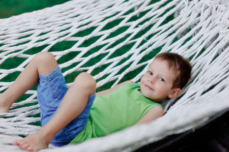 vacationing: Boy in green shirt swinging in a hammock on a large nature park