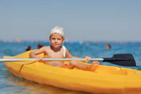 little boy swimming in the yellow boat on the sea photo