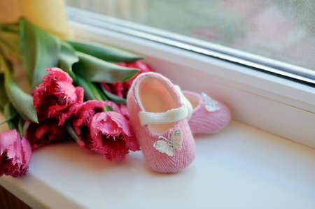 on the window sill is a bouquet of pink tulips and children s slippers photo