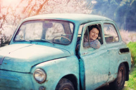 beautiful girl sitting in an old car and smiling with pleasure photo