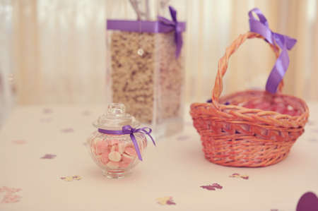 glass vase and a jar with purple ribbon and wicker basket photo