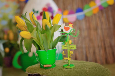 in a green bucket bouquet of yellow tulips and a toy chicken photo