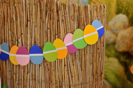 weighs: Easter composition, on a bamboo fence weighs garland of colored eggs