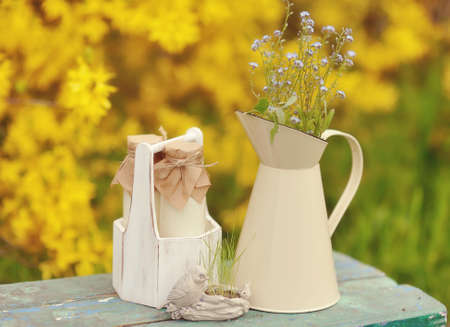 on a yellow background with a jug of wild flowers and bottles photo